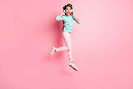 Full length body size photo of crazy little hispanic girl jumping up shouting wearing earphones isolated on pink color background