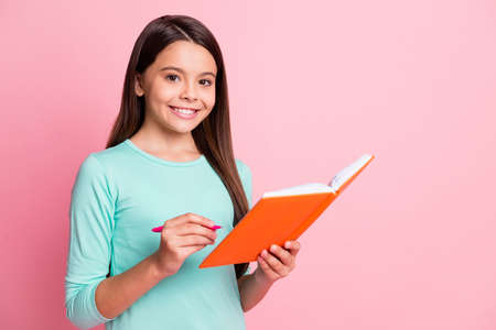 Photo of lovely cute little intelligent hispanic lady long hairstyle hands hold orange copybook pen write lesson white smile wear turquoise sweatshirt isolated pink color background