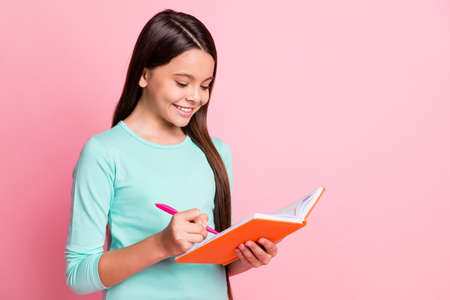 Photo of cute pretty small smart clever latin lady long hairdo arms hold orange diary purple pen write notes toothy smile wear turquoise teal sweatshirt isolated pink color background 스톡 콘텐츠