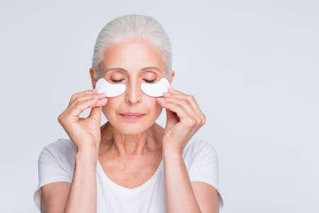 Close up photo of lovely retiree with closed eyes applying nourishment under eyes wearing stylish trendy t-shirt isolated over white background Stock Photo