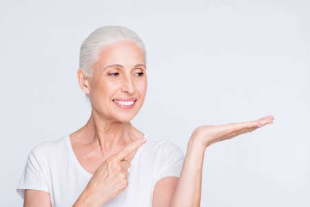 Close-up portrait of her she nice-looking attractive lovely cheerful cheery confident gray-haired lady holding on palm solution tips feedback new novelty isolated on light white grey background Foto de archivo