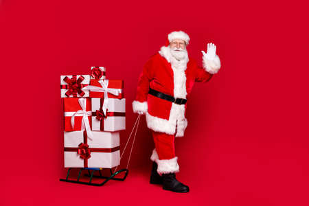 Photo portrait of funky white bearded man in santa claus costume pulling stack of presents on sleigh waving hand isolated on bright red colored background