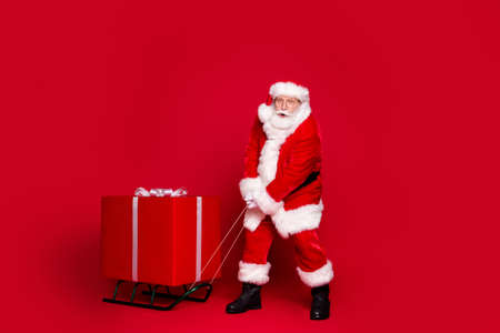 Photo portrait of white bearded santa claus not strong enough to pull present on sleigh isolated on vivid red colored background Imagens
