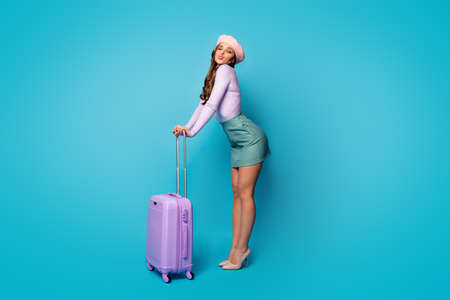 Full length body size view of nice attractive lovely pretty winsome slim fit cheerful wavy-haired girl tourist holding bag sending kiss isolated on bright vivid shine vibrant blue color background