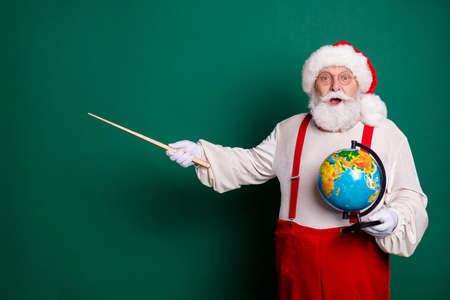 Portrait of his he nice handsome cheerful amazed genius clever smart bearded fat Santa professor holding in hands globe showing copy space science solution idea look isolated green color background