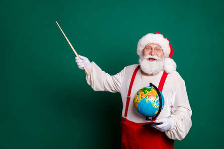 Portrait of his he nice handsome cheerful brainy genius clever smart bearded fat Santa professional tutor holding in hands globe showing copy space science solution isolated green color background 免版税图像