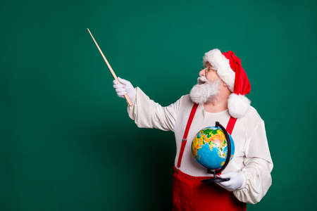 Portrait of his he nice handsome cheerful knowledgeable clever smart fat bearded Santa professional teacher holding in hands globe showing copy space science lesson isolated green color background