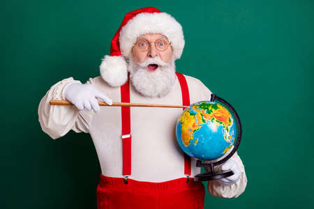 Portrait of his he handsome cheerful amazed clever fat bearded Santa professional teacher holding in hands globe showing country continent map planet science lesson isolated green color background