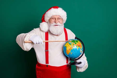 Portrait of his he nice handsome cheerful smart clever bearded fat Santa teacher holding in hands globe pointing country continent ecology lesson map planet science isolated green color background