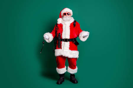 Full length body size view of his he nice attractive funky funny bearded Santa grandfather holding in hands whip tools toys playing game party inviting you isolated over green color background