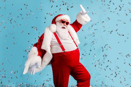 Photo of pensioner old man grey beard careless north pole closed party dance having fun colorful confetti wear santa x-mas costume suspender sunglass cap isolated blue color background