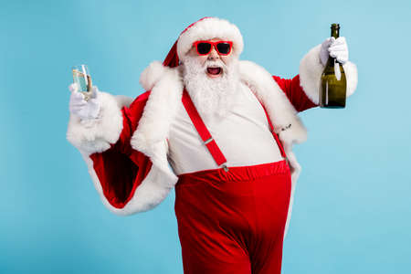 Photo of retired old man grey beard funky hold bottle full glass golden wine drink having fun open mouth wear santa x-mas costume suspender sunglass cap isolated blue color background