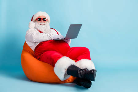 Full length photo of pensioner old man beard hold netbook take remote order north pole sit orange bean bag wear santa x-mas costume suspender sunglass boot cap isolated blue color background Stock Photo