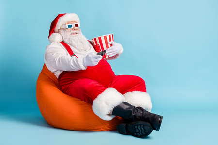 Full length photo of retired old man grey beard hold remote controll bucket watch sit orange beanbag wear red santa x-mas costume suspender 3d glasses cap boot isolated blue color background
