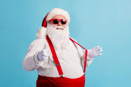 Portrait of his he nice attractive cheerful confident flirty thick white-haired Santa pointing at you date invite pulling suspender isolated bright vivid shine vibrant blue color background Stock Photo