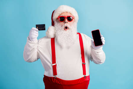 Portrait of his he attractive amazed white-haired Santa holding in hand demonstrating credit card gadget order shop buy good product cash back isolated bright vivid shine vibrant blue color background
