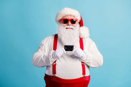 Portrait of his he nice attractive cheerful cheery white-haired Santa holding in hands using credit card order shopping service cash back isolated bright vivid shine vibrant blue color background