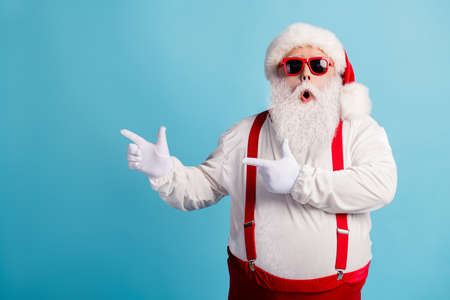 Portrait of his he nice attractive amazed wondered overweight white-haired Santa demonstrating copy space solution advice attention isolated over bright vivid shine vibrant blue color background