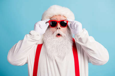 Close-up portrait of his he nice attractive amazed funky white-haired father Santa touching specs season sale discount isolated over bright vivid shine vibrant blue color background
