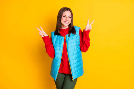 Photo of charming attractive girl have enjoy autumn fall holiday make v-sign wear season good look clothes pants isolated over shine color background Foto de archivo