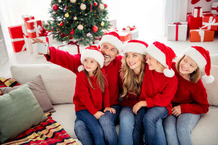 Full family x-mas vacation. People mommy mom daddy dad three preteen little kids sit sofa make selfie smartphone in house indoors with christmas tree time noel tinsels wear santa claus hats Stock Photo