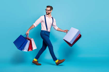 Full length profile photo of handsome business man carry many bags buy vacation stuff shopping center good mood wear specs shirt suspenders pants boots isolated blue color background