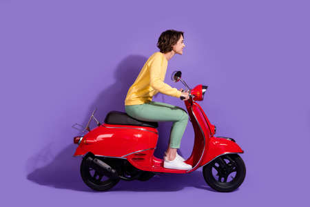 Full length body size side profile photo of young girl wearing casual outfit driving red motorcycle smiling looking forward isolated on vivid purple color background