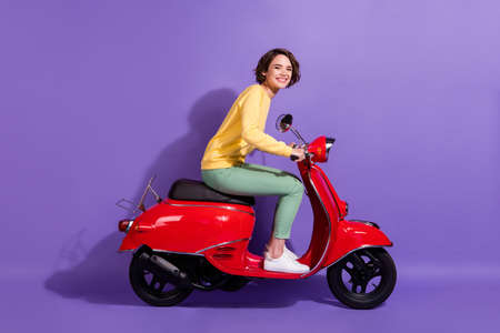 Full length body size profile photo of brunette pretty student driving retro red moped smiling happily isolated on bright purple color background Banco de Imagens