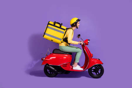 Profile side view of her she nice attractive cheerful girl riding bike delivering shop cafe order fast speed express isolated over bright vivid shine vibrant lilac violet purple color background Standard-Bild