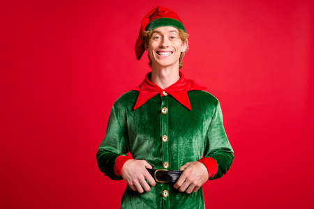 Photo of funky elf guy touch his black belt happy christmas x-mas newyear event concept isolated on bright shine color background Stockfoto