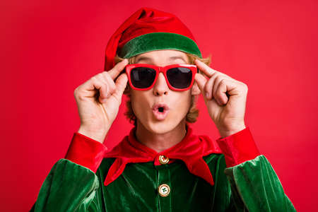 Portrait of astonished elf guy look x-mas christmas discounts touch hands specs isolated on bright red color background Stockfoto