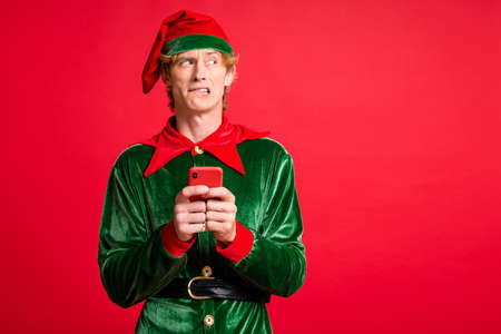 Photo of scared elf guy hold smartphone look copyspace bite lips wear green headwear isolated on bright red color background