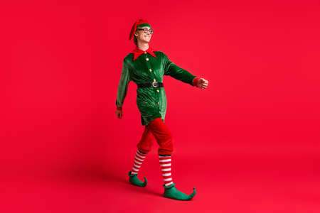 Full body photo of positive cheerful elf guy go copyspace isolated over red vibrant color background