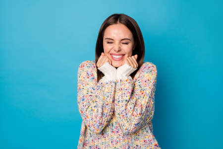 Photo of funny attractive cheerful lady good mood arms on chin cheeks eyes closed overjoyed birthday girl see many presents wear casual warm sweater isolated blue color background Foto de archivo