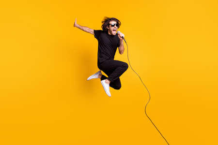 Full length photo of young man jump raise hand hold mic open mouth wear black t-shirt pants white sneakers sunglass isolated yellow color background