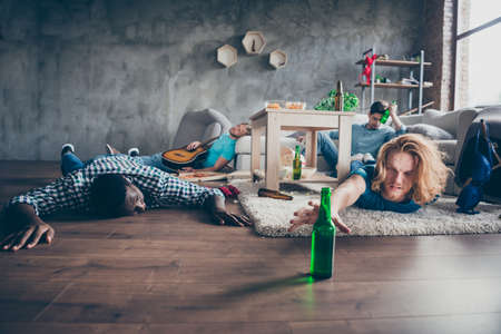 Photo of unwell being blonde hair man have lifestyle crazy party with fellows feel hangover want drink reach hand bottle lie floor pals sleep in house indoors Stockfoto