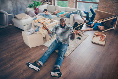 I cant remember party night. Top above high angle view full body photo of afro american guy sit floor hold empty beer bottle shrug shoulders have handover his buddies sleep in house indoors