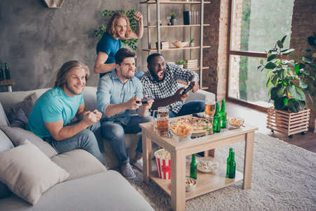 Full length photo of focused guy sit cozy couch play joystick want win two blonde hair pals support raise fists have table with crisps chips pint bottle in house indoors