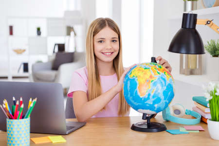 Photo of positive girl child sit table desk study remote use globe want explore earth continent in house indoors
