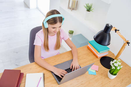 Top above high angle view photo little kid girl study remote use laptop text type have online communication conversation tutor have headset sit comfort cozy table desk in house indoors