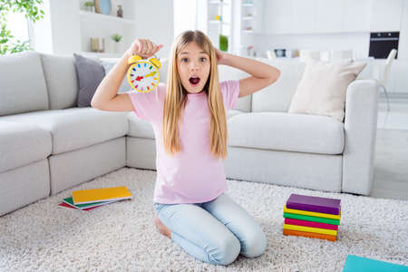 Oh no i miss online lesson. Full size photo of amazed frustrated kid girl sit floor carpet hold clock touch hand head scream omg in house indoors 免版税图像