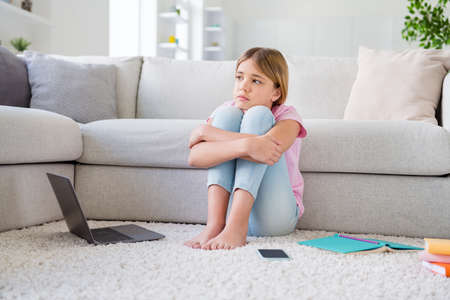 When we go to school. Full size photo of frustrated kid girl tired study remote corona covid virus quarantine look imagine infection stop spreading sit floor carpet in house indoors Stock Photo