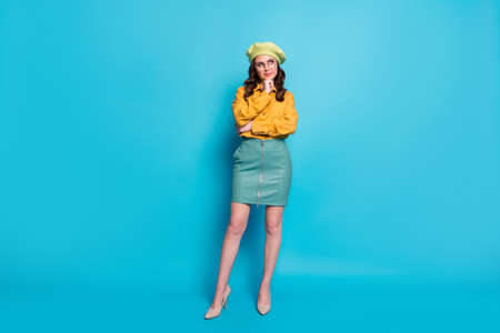 Full size photo of minded girl touch chin fingers look copyspace think thoughts decide choose decisions choice wear headwear isolated over blue color background