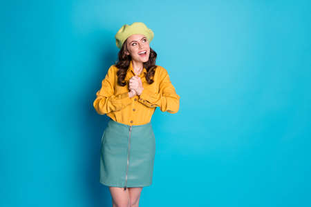Photo of positive cheerful girl impressed wish desire present gift ads look copyspace impressed wear headwear isolated over blue color background