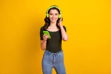 Portrait of her she nice attractive lovely cheerful cheery wavy-haired girl enjoying listening music spending free spare time isolated on bright vivid shine vibrant yellow color background Stock fotó