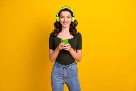 Portrait of her she nice attractive lovely pretty cheerful cheery wavy-haired girl listening music spending weekend isolated on bright vivid shine vibrant yellow color background