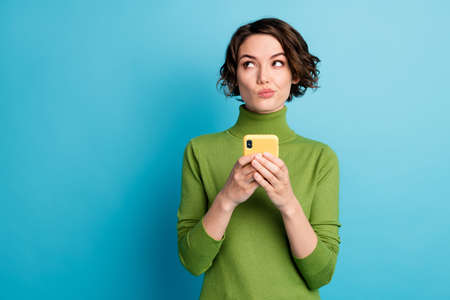 Photo of minded unsure girl use smartphone want type text dont know what about wear green style stylish trendy pullover isolated blue color background