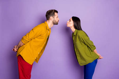 Profile photo of lady guy couple eyes closed visit blind date first kiss tender blow lips waiting contact hands behind back wear colorful shirts trousers isolated purple color background