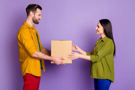 Profile side view portrait of his he her she nice attractive pretty careful cheerful cheery couple guy giving parcel shop isolated bright vivid shine vibrant lilac violet purple color background