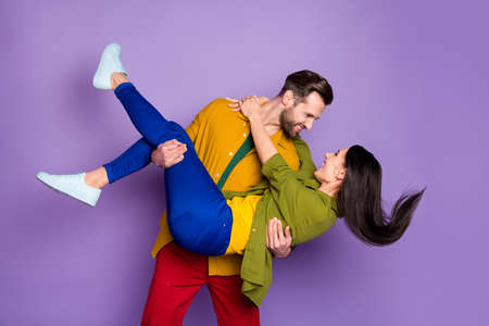 Photo pretty lady handsome fiance guy couple carry wife bride hold arms playful wedding day look eyes tempting wear casual bright shirts pants outfit isolated purple color background